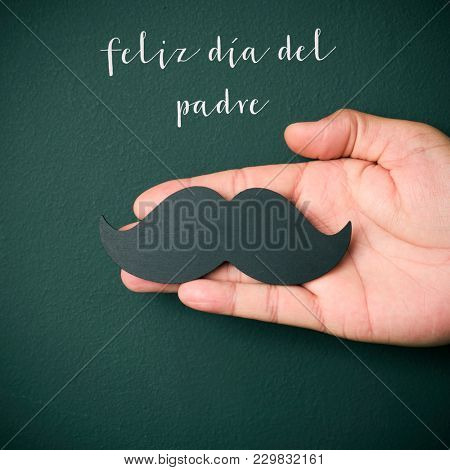 the text feliz dia del padre, happy fathers day in spanish, and the hand of a young caucasian man holding a mustache depicting a man face, on a dark green background