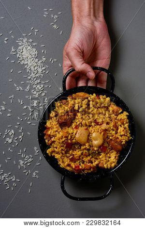 high angle shot of a young caucasian man holding a typical spanish paella valenciana in a typical paella pan, on a gray rustic table