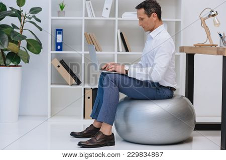Side View Of Handsome Mature Businessman Working With Laptop While Sitting On Fit Ball