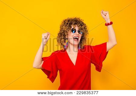 Portrait Of A White Woman With Afrro Curly Hairstyle In Red Dress And Sunglasses Holding Fists Up In