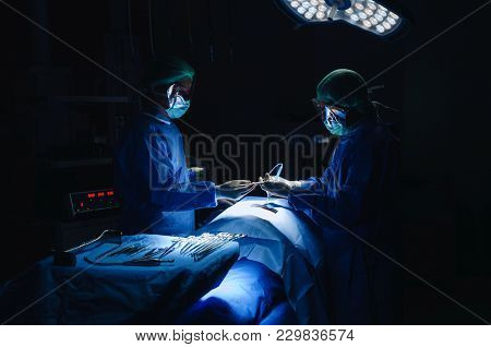 Doctor And Assistant Surgeon Surgical Instrument Sending To Hand Work For Rescue Patient In Operatio