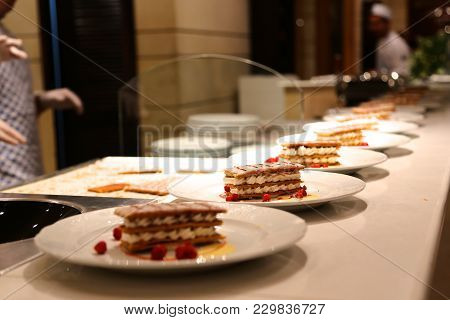 Sweet Dessert - On Several Plates Handmade Cream  Cakes Are Strewed With A Fresh Wild Strawberry