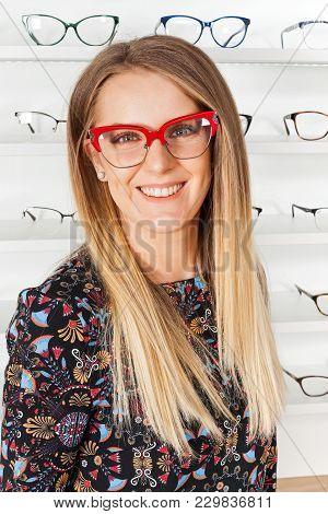 Seductive Blond Woman Choosing Eyeglass Frame In An Optical Store