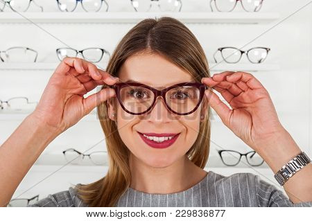 Attractive Young Woman Choosing Eyeglass Frame In An Optical Store, Fashion & Style