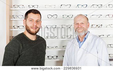 Mature Ophthalmologist With Young Man Choosing Eyeglass Frame In Optical Store