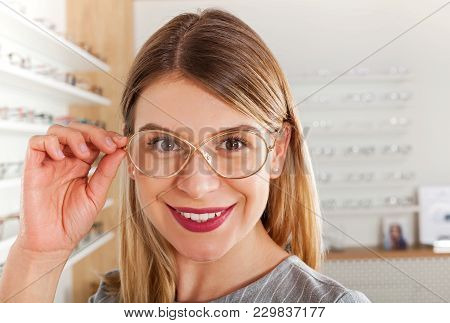 Attractive Young Woman Choosing Eyeglass Frame In An Optical Store