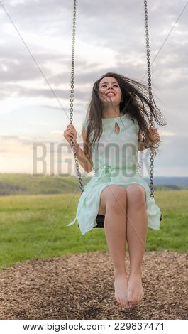 Happy Young Woman On A Swing At Sunset - Beautiful Brunette Woman, Dressed In A Cute Green Dress, Wi