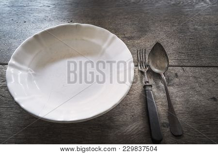 Vintage Aged Plate And Cutlery - White Vintage Plate And Old Rusty Metal Tableware,  On An Aged Wood