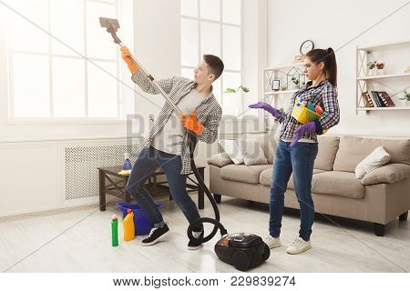 Young Couple Cleaning Home, Man Playing With Vacuum Cleaner, Having Fun In Living-room. Housekeeping