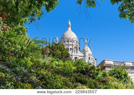 Green flowerbed with flowers as famous Sacre-Coeur Basilica on background under blue sky in Paris, France.