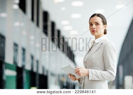 Pensive businesswoman in elegant formalwear browsing in the net on the move