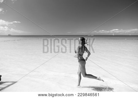 Girl In Bikini Running On Beach With White Sand, Turquoise Sea Or Ocean Water And Blue Sky On Sunny