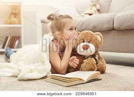 Cute Happy Little Casual Girl Embracing Teddy Bear, Reading Book And Sharing Secrets With Her Favori