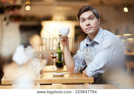 Young businessman drinking coffee at restaurant after hard work