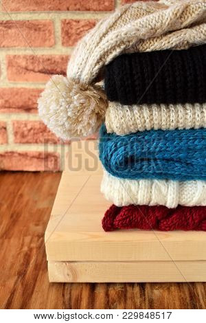 Knitted Scarves Of Different Colours And A Hat Are Piled Carefully