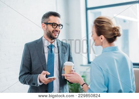 Business Partners Talking In Office While Drinking Coffee