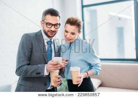 Businessman Showing His Smartphone To Collleague While Having Coffee To Go