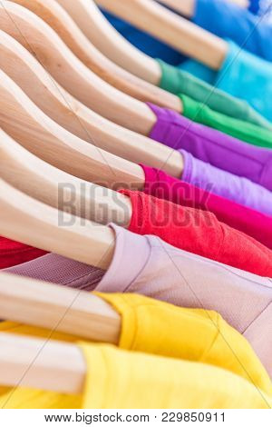 Clothing rack hangers in wardrobe closet at shopping store. Rainbow selection of colorful t-shirts tops for spring fashion style. Organization by color of closet at home.