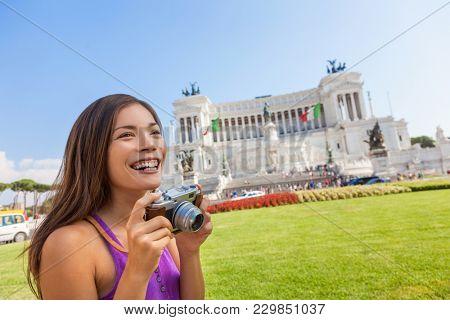 Italy tourist Asian woman taking travel photo with vintage camera at Monumento Nazionale vittorio emanuele ii,The Altare della Patria, or Il Vittoriano, Rome, Italian building. Europe vacation.