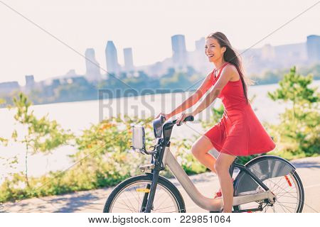 City bike young woman biking riding bicycle in street outdoors in summer with city skyline. Happy multiracial Asian girl active living a healthy lifestyle. Urban living, commute going to work.