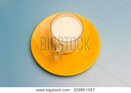 Milk In A Glass Cup On A Yellow Saucer On A Blue Background