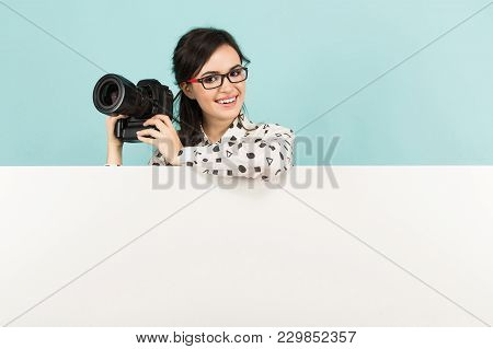 Portrait Of Young Attractive Happy Woman Photographer In White Shirt Holding Camera Over White Banne