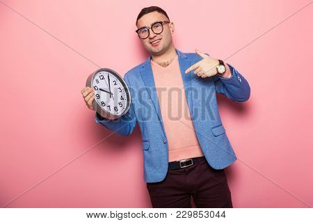 Portrait Of Handsome Man In Eyeglasses, Pink Jumper And Blue Jacket Pointing At Watches Isolated On