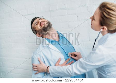 Female Doctor Listening To Heartbeat Of Colleague Who Has Heart Attack With Stethoscope