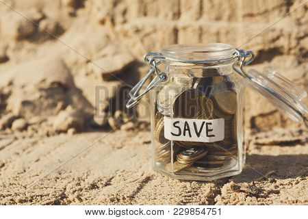 Coins In Glass Jar On Rock Background, Copy Space. Money Box, Saving Money For Dream, Pension, Vacat