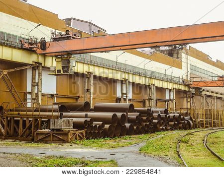 Industrial Area. Outdoors Crane Trestle. Overhead Traveling Crane Above The Open Warehouse And Loadi