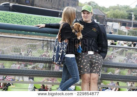 A Man And A Woman With A Dog In Her Arms Standing Beside The Canal Near King's Cross