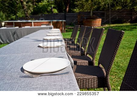 Dinner Table With Empty Ceramic Round Plates And Cutlery On Grey Tablecloth And Chairs In Garden Out