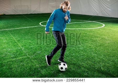 Young man in sportswear running before soccer ball on green pitch during training