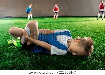 Little player lying on pitch and suffering from pain in his knee or leg after falling
