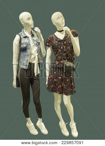 Two Full-length Female Mannequins Dressed In Fashionable Clothes, Isolated On Green Background. No B