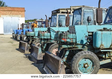 Russia, Temryuk - 15 July 2015: Tractor. Bulldozer And Grader. Tractor With A Bucket For Digging Soi