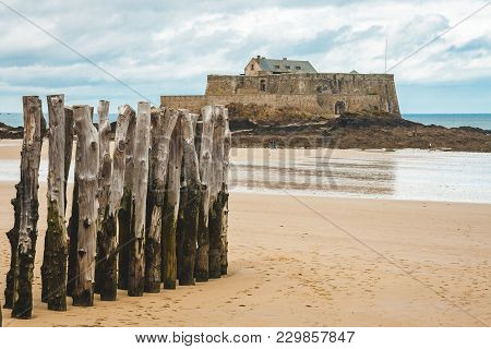 Wooden Poles On Sea Shore During Low Tide And Fort National, 17-century Fortress On Island In Saint-