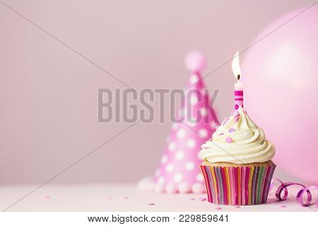 Birthday cake with single candle and party balloon