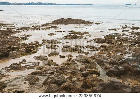 Brown Damp Stones, Rocks And Wet Sand Revealed During Low Tide On Sea Shore