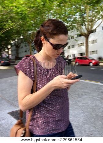 Adult Woman, (age 30) Walking And Text Messaging In City Street At The Same Time. Mobile Communicati