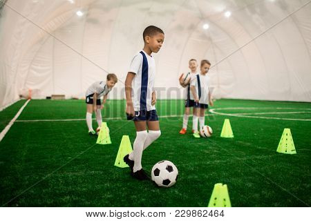 One of boys in football uniform training with ball on green pitch with cones