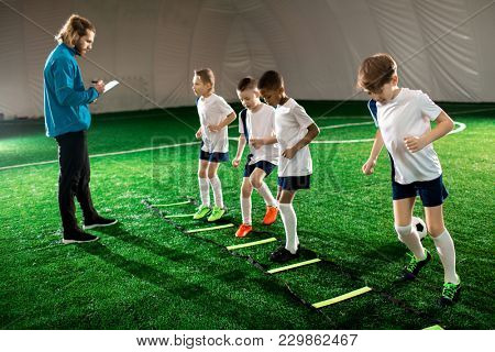Trainer writing down results of little football players while they exercising on pitch facilities