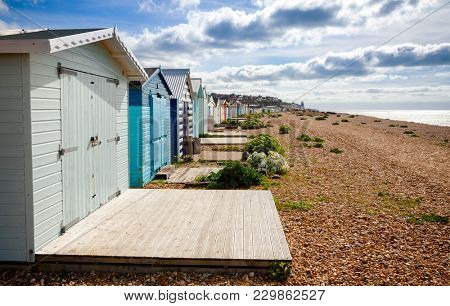 Row of wooden cabins on shingle beach at popular seaside resort Hastings in East Sussex South East England UK
