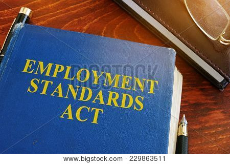 Employment Standards Act And Glasses On A Desk.