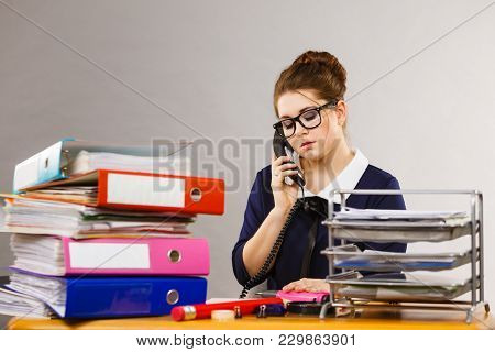 Business Woman Sitting Working At Desk Full Off Documents In Binders Talking With Someone On Phone