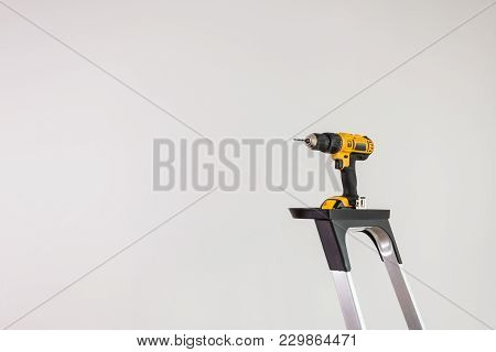 Repairing, Work Tools. Professional Battery Drill Standing On Ladder. Gray Light White Background Wi