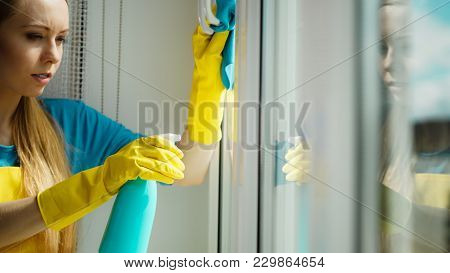 Young Woman In Yellow Gloves Cleaning Window With Blue Rag And Spray Detergent. Spring Cleanup, Hous