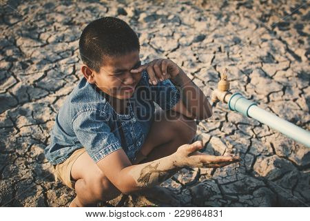 Sad Boy Want To Drink Some Water On Crack Ground , Concept Drought And Shortage Of Water Crisis
