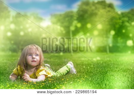 Portrait Of A Smiling Little Girl Lying On Green Grass Cute Three Years Old Child Enjoying Nature Ou