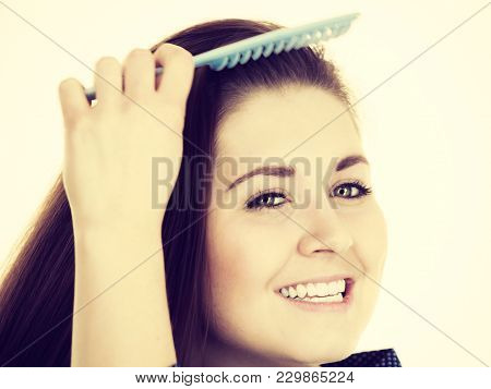 Woman Combing Her Healthy Hair Using Comb. Young Latin Female With Beautiful Natural Brown Straight